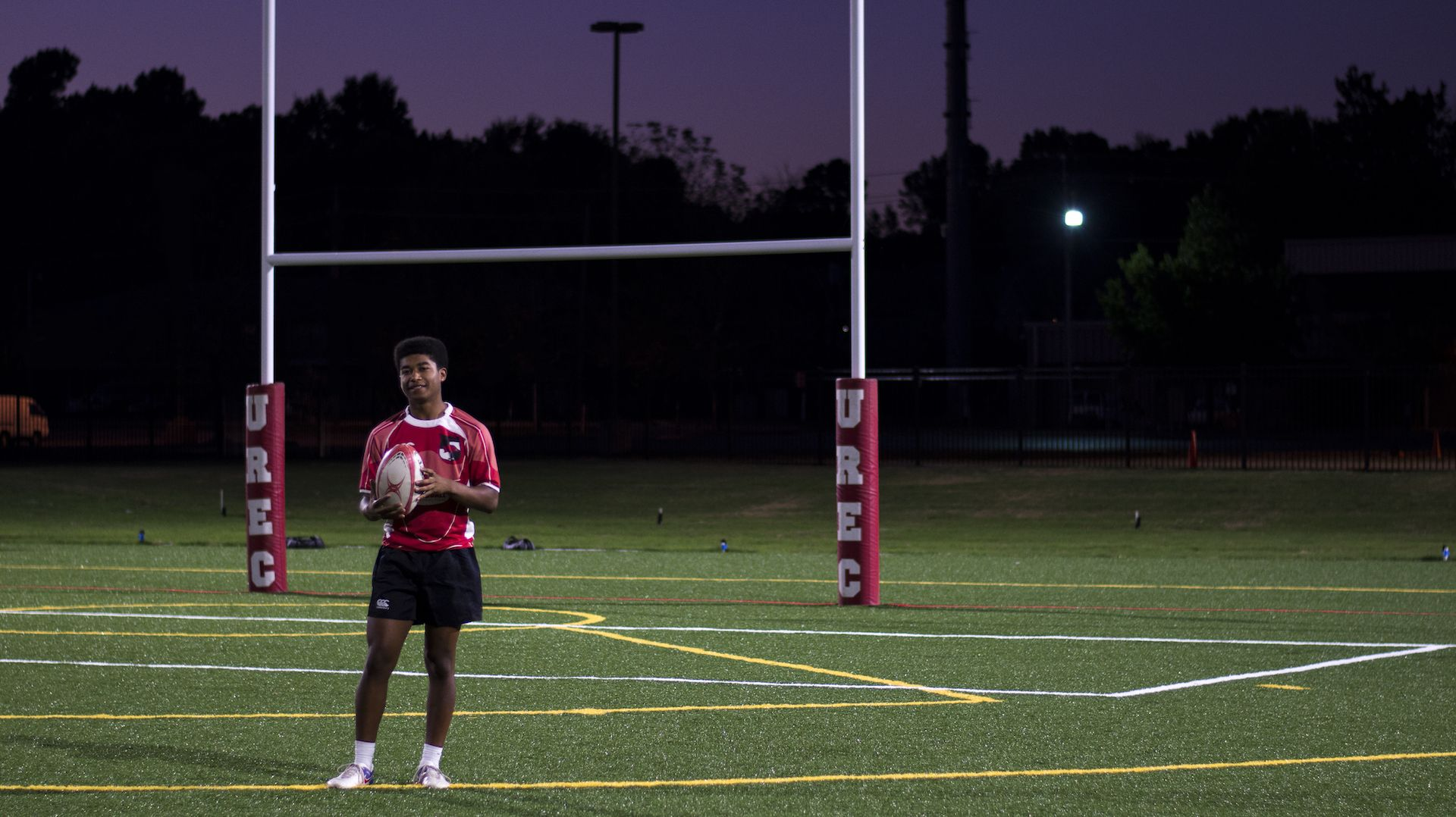 Arkansas men's rugby team member holding rugby ball