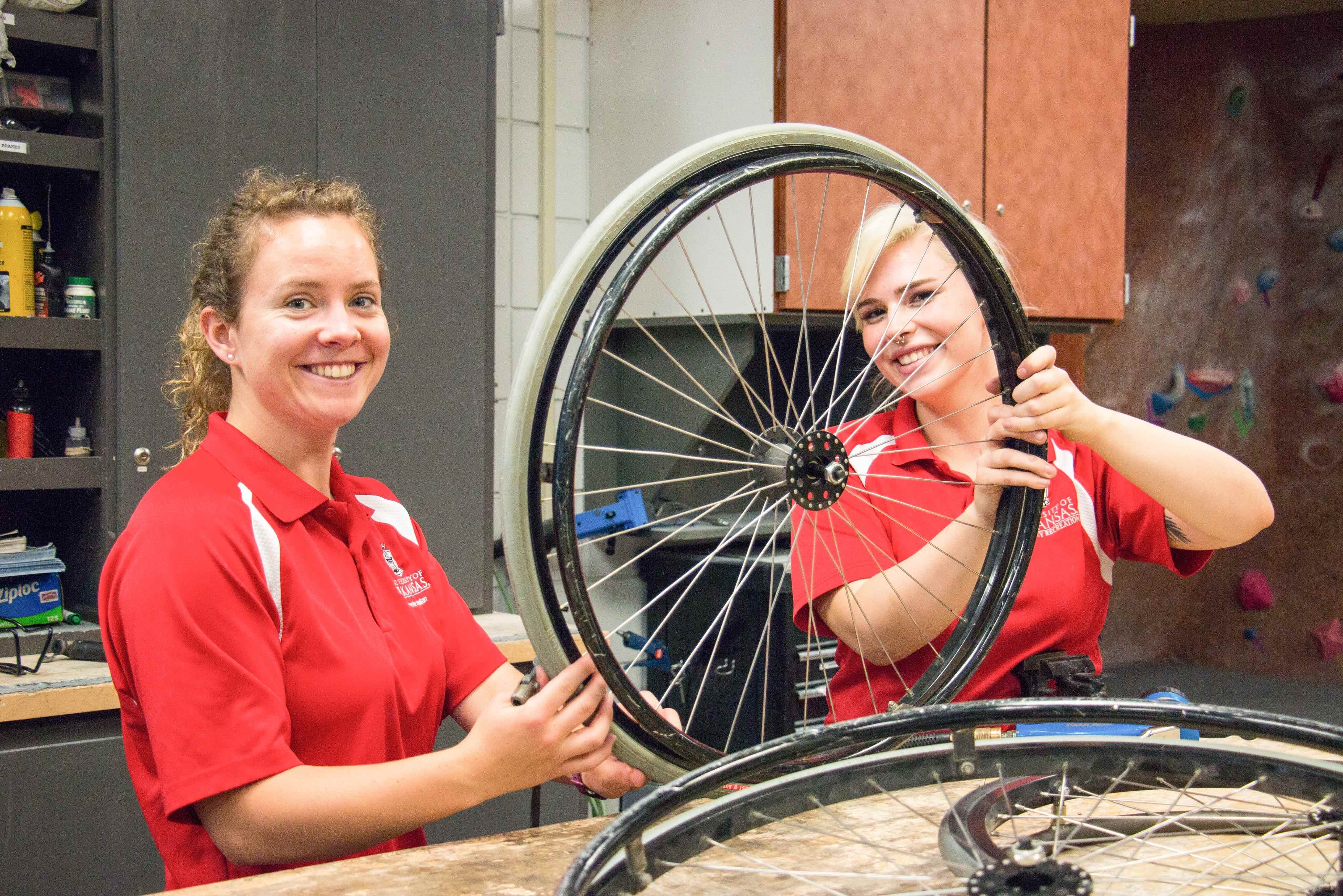 two women working on a bike wheel