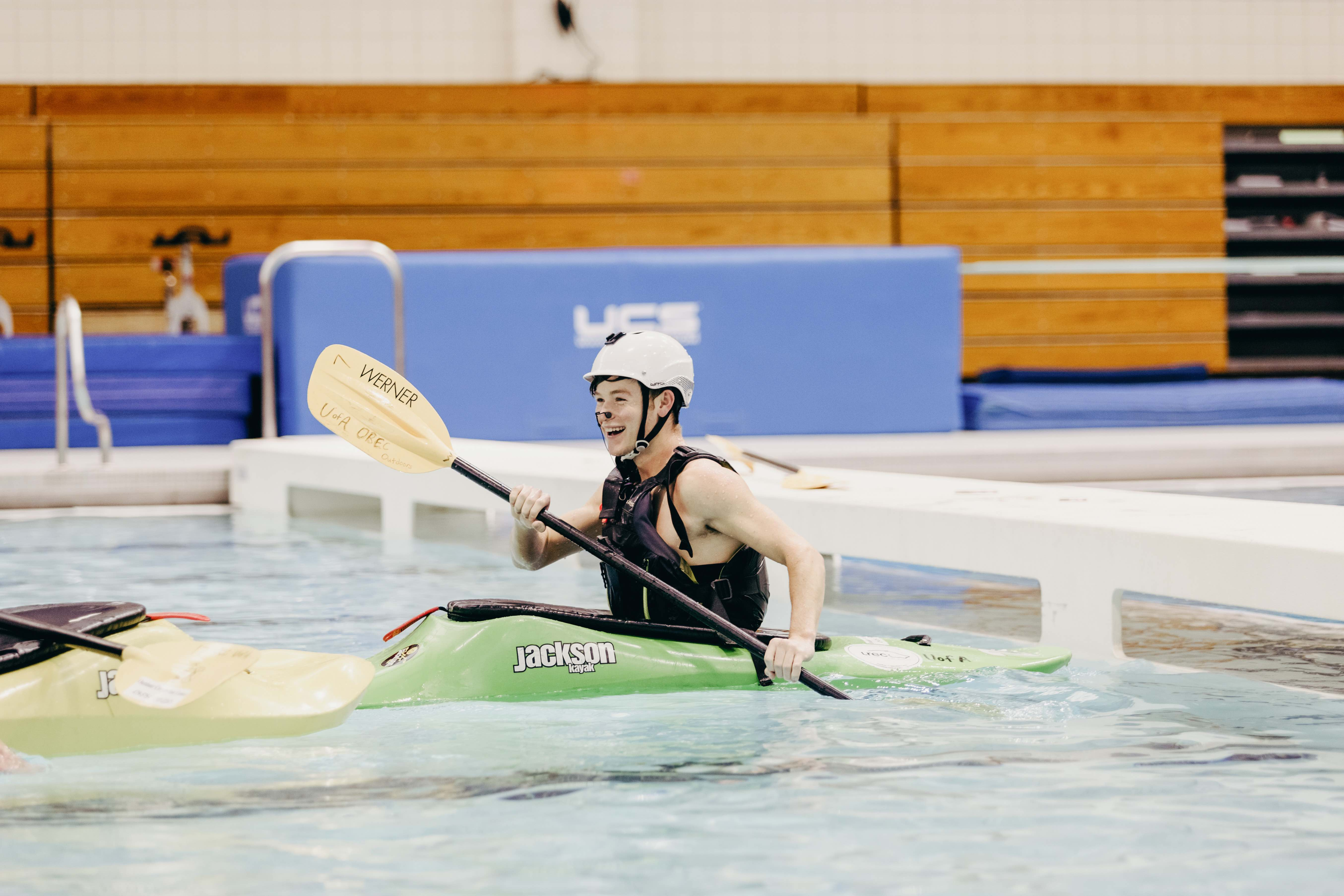 man in whitewater kayak practicing skills in a pool